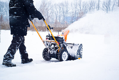 Man operating a snowblower in winter snow